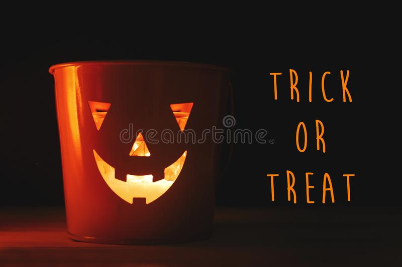 Happy Halloween text sign. Halloween Jack o lantern with glowing. Face in dark black background isolated. Glowing spooky face on bucket. Space for text. Season` royalty free stock image
