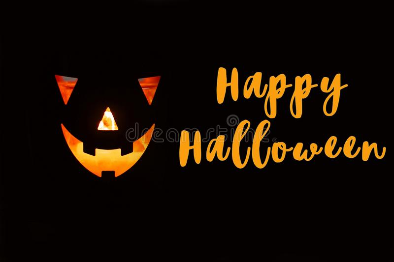 Happy Halloween text sign. Halloween pumpkin with scary glowing. Face on black background isolated. Jack-o-lantern glowing pumpkin in dark. Season`s greeting stock photography
