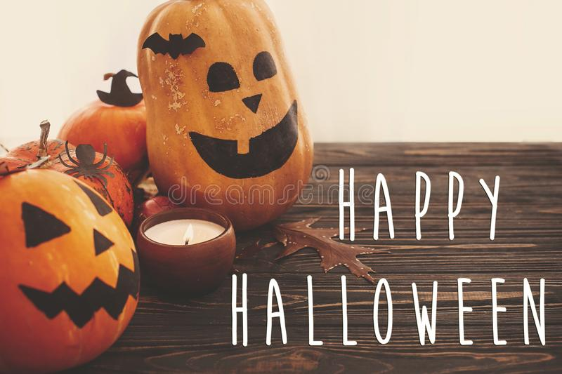 Happy Halloween text sign on pumpkins, jack-o-lantern, witch cauldron, bats, spider, candle, autumn leaves on black wood in light. Halloween decoration. Season stock photography