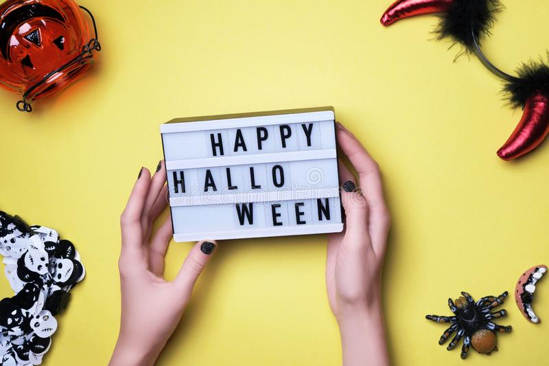 Happy Halloween text in woman hands, party inventory. Halloween words on white board, devil horns, spider, pumpkin royalty free stock photo