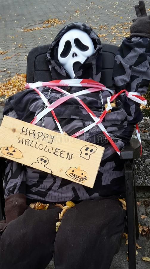 Happy Halloween. A tied up figure with a skull Facebook and a placard wishing a happy Halloween royalty free stock photo