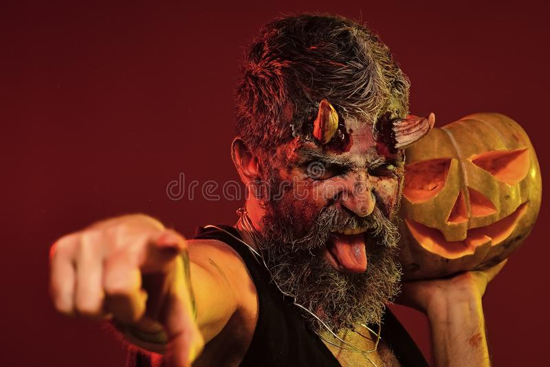 Happy Halloween trick or treat. Satan show tongue with bloody horns, beard, blood, wounds. Demon point finger with jack o lantern. Darkness and light concept stock images