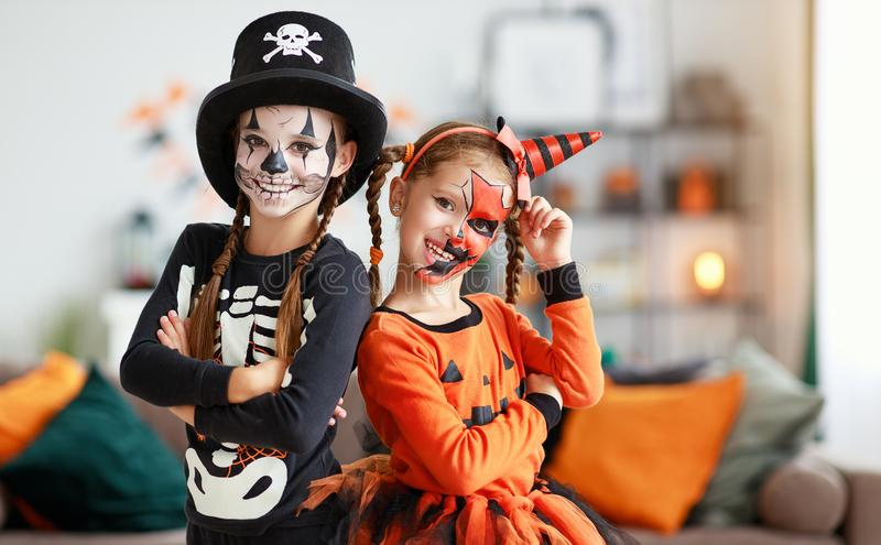 Happy Halloween! two children in suits and with pumpkins in home royalty free stock photo