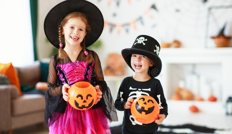 . happy Halloween! two children in suits and with pumpkins in home. Happy Halloween! a two of children in suits and with pumpkins in home stock photo