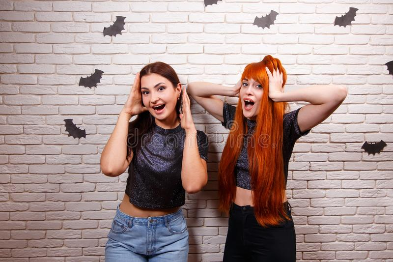 Happy Halloween! Two young cute scared women partying and having. Fun over Halloween decorations royalty free stock photography