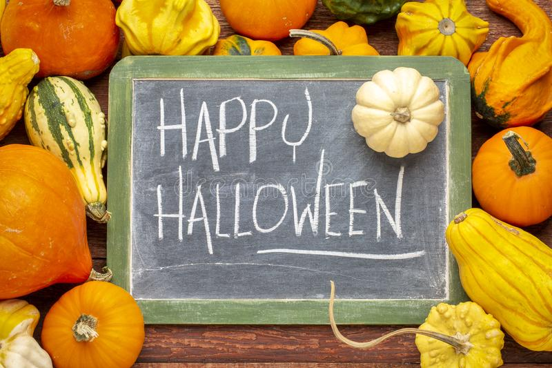 Happy Halloween on blackboard with squash. Happy Halloween - white chalk handwriting on a slate blackboard surrounded by winter squash and gourds royalty free stock images