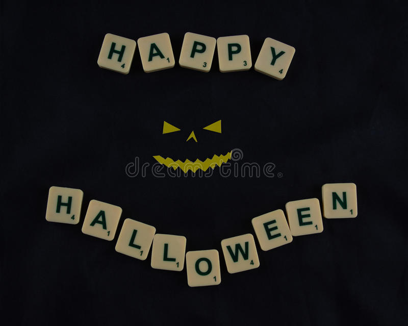 Happy Halloween. Wishes on a black background and a smiling demon face royalty free stock photography