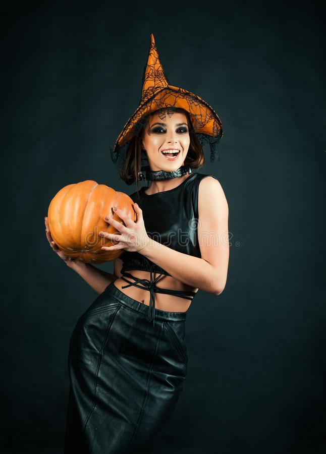 Happy Halloween Witch with bright make-up.Celebration autumn holiday Halloween. Halloween Witch with a carved Pumpkin. royalty free stock photos