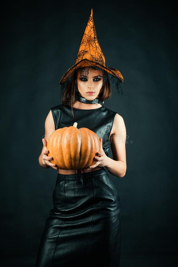 Happy Halloween witch with pumpkin. Witch magic. Sexy girl in Halloween costume. Secrets of magic. royalty free stock photo