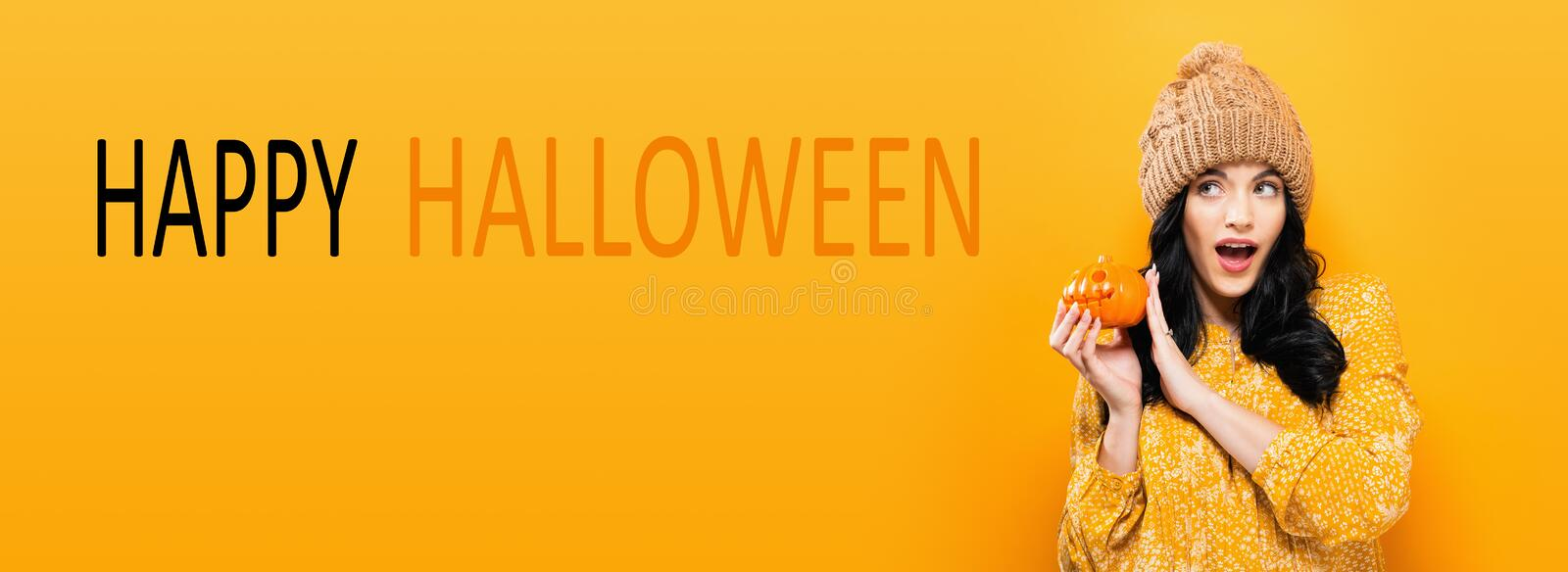 Happy Halloween with woman holding a pumpkin. Happy Halloween with young woman holding a pumpkin stock photo