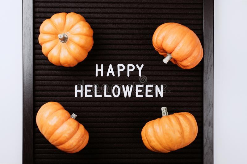 Happy Halloween words on black letter board in frame with pumpkins. Happy Halloween words on black letter textured board. It is in frame with small yellow royalty free stock photos