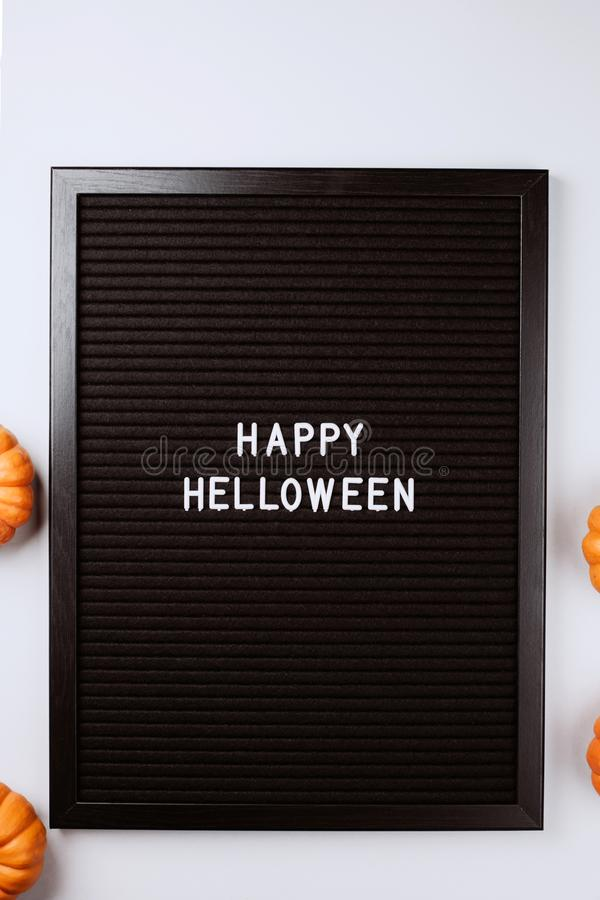 Happy Halloween words on black letter board with pumpkins on white background. Happy Halloween words on black letter textured board. It is in frame with small stock photo