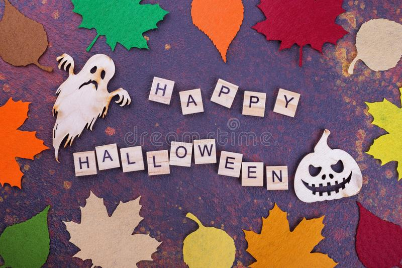 Happy Halloween words with wooden decoration. Scary wooden ghost and pumpkin. Dark postcard to Halloween royalty free stock photo