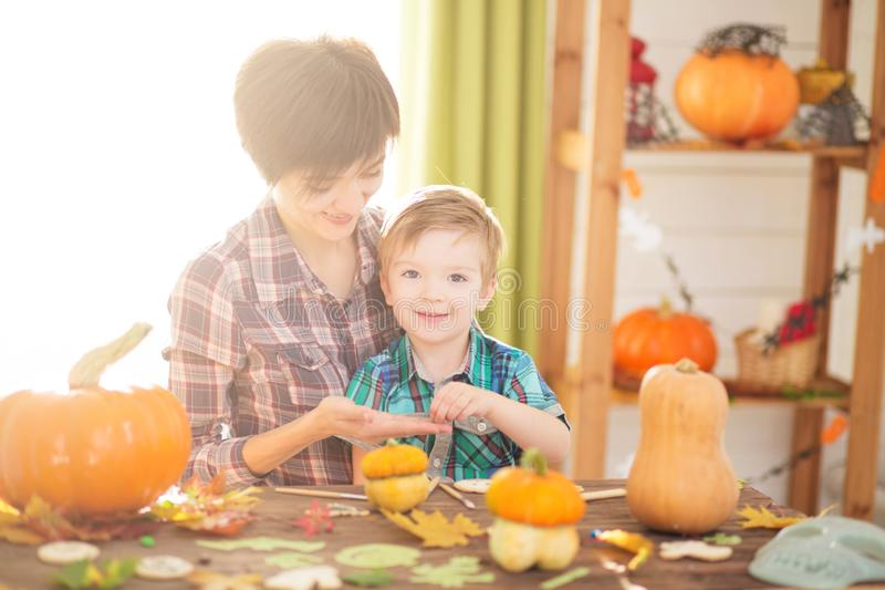 Happy Halloween. Young woman with her little son are preparing to Halloween on kitchen. Mother with son are having fun with pumpki. Happy Halloween. Young women stock images