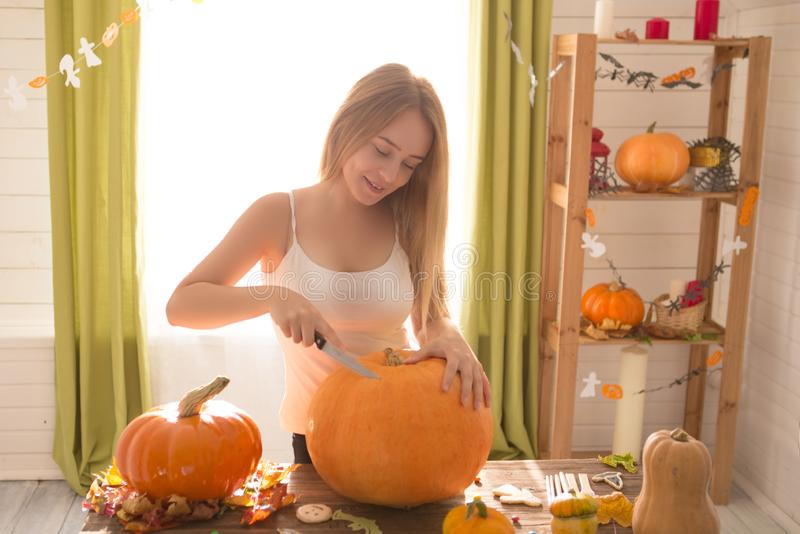 Happy Halloween! Young woman preparing for Halloween in the kitchen. Beautiful woman with pumpkins.  royalty free stock photo