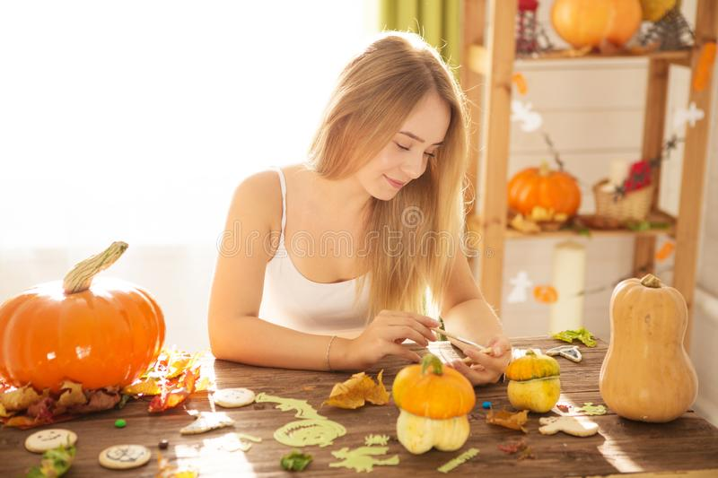 Happy Halloween! Young woman preparing for Halloween in the kitchen. Beautiful woman with pumpkins.  stock photos
