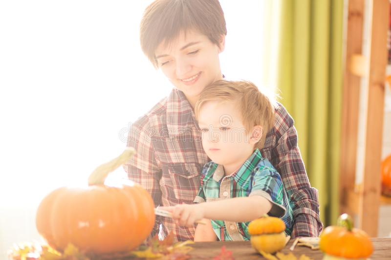 Happy Halloween. Young woman with her little son are preparing to Halloween on kitchen. Mother with son are having fun with pumpki. Happy Halloween. Young women stock photo