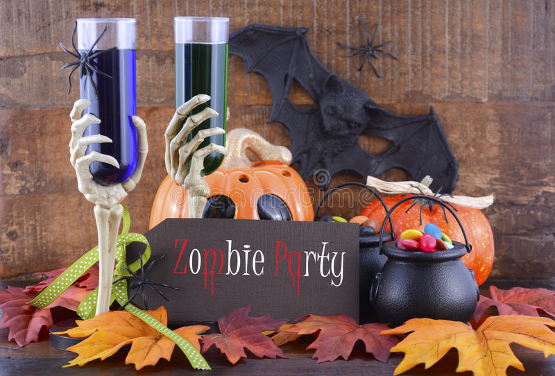 Happy Halloween Zombie Party Decorations. Happy Halloween Zombie Party decorations with green and blue drinks in skeleton hand glasses, pumpkins and candy on stock image