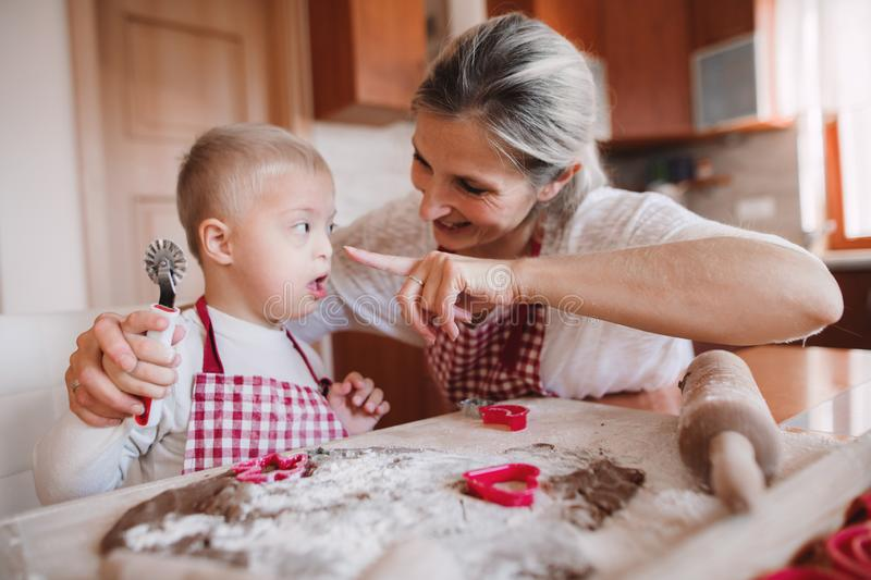 A happy handicapped down syndrome child with his mother indoors baking. A happy handicapped down syndrome child and his mother with checked aprons indoors stock photo
