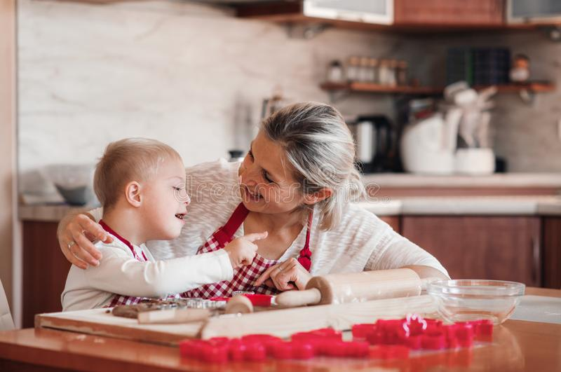 A happy handicapped down syndrome child with his mother indoors baking. A happy handicapped down syndrome child and his mother with checked aprons indoors stock images