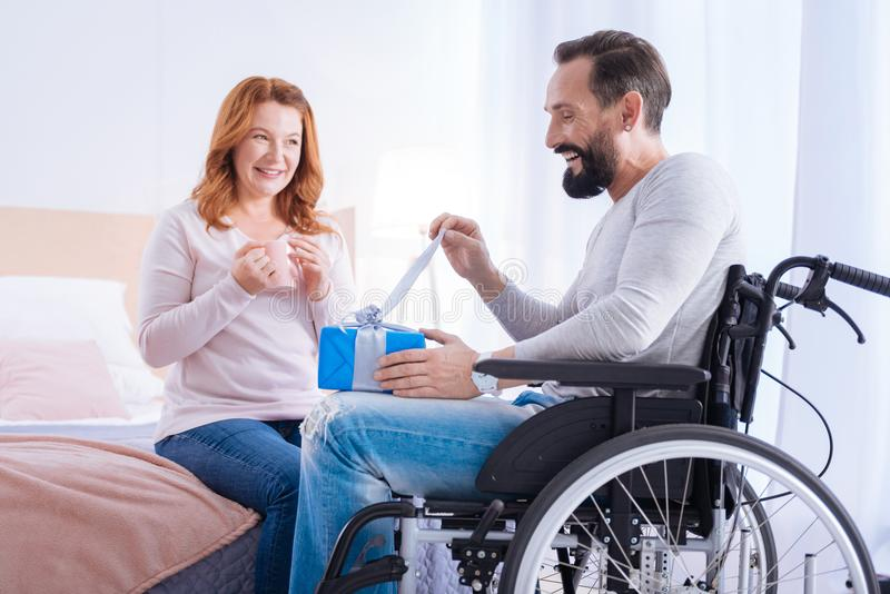 Happy handicapped man opening a gift. Opening the gift. Bearded disabled men opening a present while sitting in a wheelchair and a smiling women sitting on the royalty free stock photography