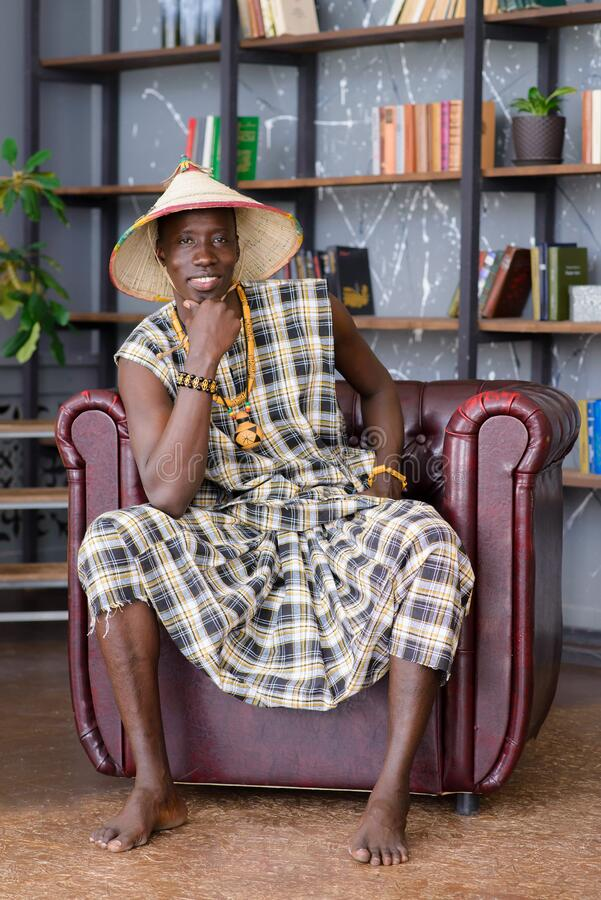 Happy Handsome african man in traditional clothes sitting on chair.  royalty free stock photography