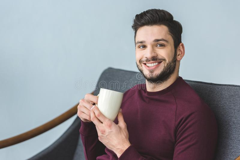 happy handsome bearded man holding cup with drink and sitting stock image