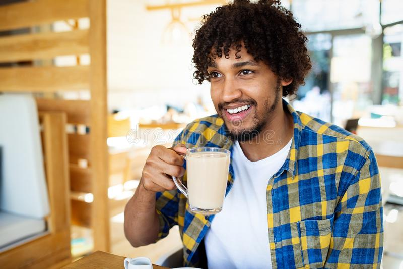 Happy handsome black man drinking coffee and smiling stock photo