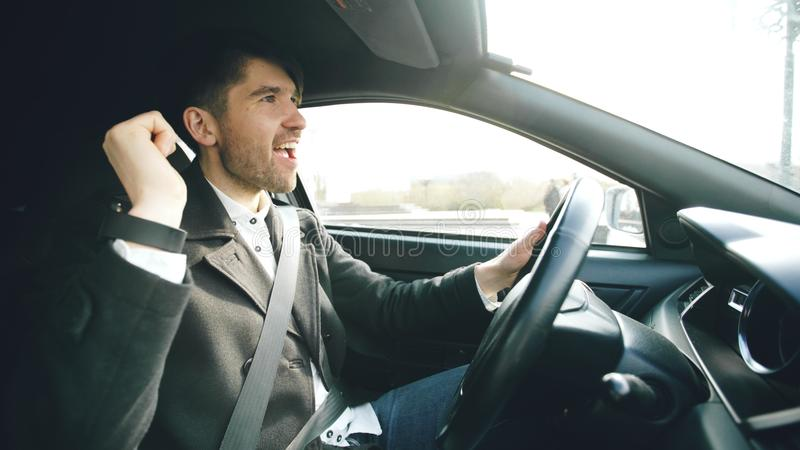 Happy handsome businessman driving car and singing. Man is happy after making deals and drives home. Happy handsome businessman driving car and singing. Man is stock photography