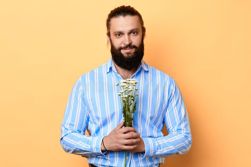 Happy handsome cheerful positive young man holding a bunch of flowers. royalty free stock image