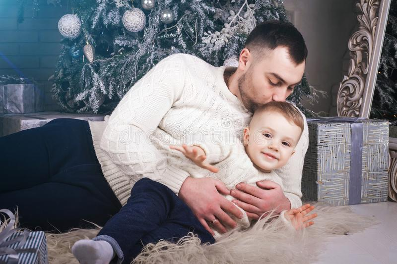 Father kissing son laying near the christmas tree royalty free stock photos