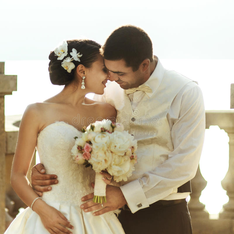 Happy handsome groom and beautifyl bride hugging on balcony at s. Unset sea background royalty free stock image