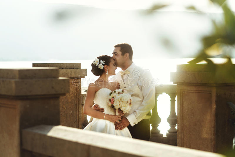 Happy handsome groom and beautifyl bride hugging on balcony at s. Unset sea background stock image