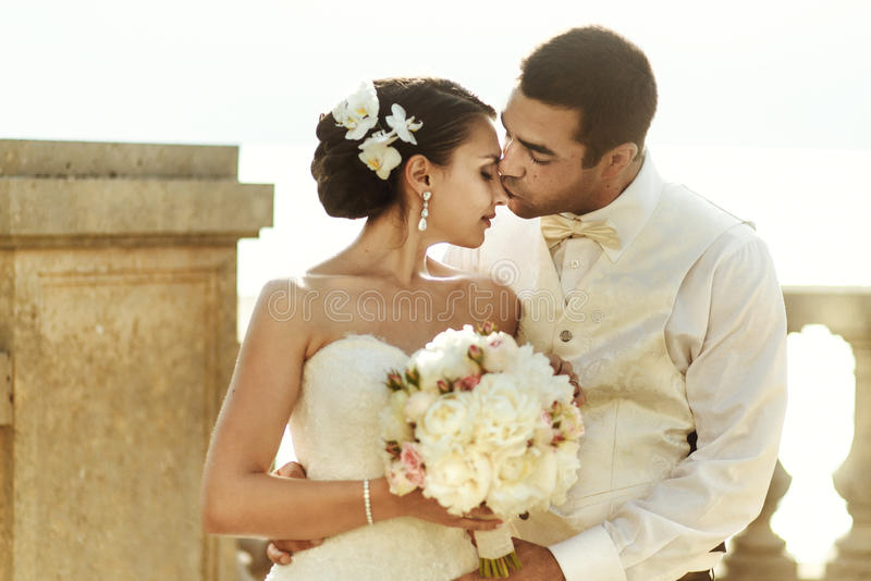 Happy handsome groom and beautifyl bride hugging on balcony at s. Unset sea background stock photography