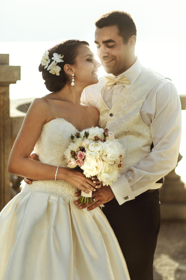 Happy handsome groom and beautifyl bride hugging on balcony at s. Unset sea background stock photo