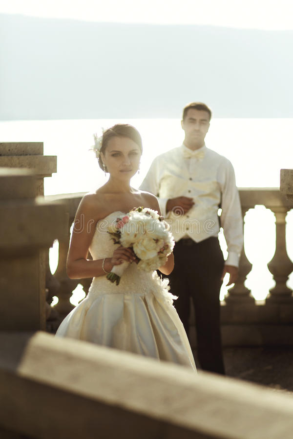 Happy handsome groom and beautifyl bride hugging on balcony at s. Unset sea background stock photos