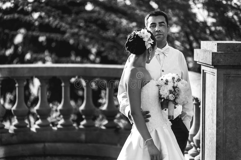 Happy handsome groom and beautifyl bride hugging on balcony at s. Unset sea background b&w royalty free stock photos
