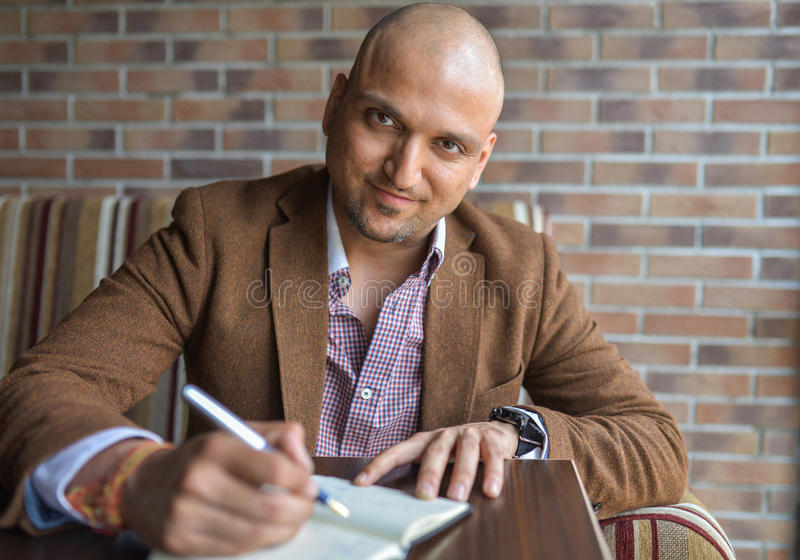 Happy handsome indian businessman making some notes in his notebook, business plan or diary writing stock image