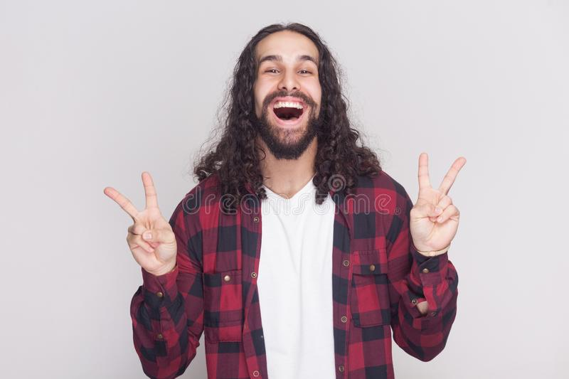 Happy handsome man with beard and black long curly hair in casual style, checkered red shirt standing with victory or peace sign. And looking at camera with stock photo