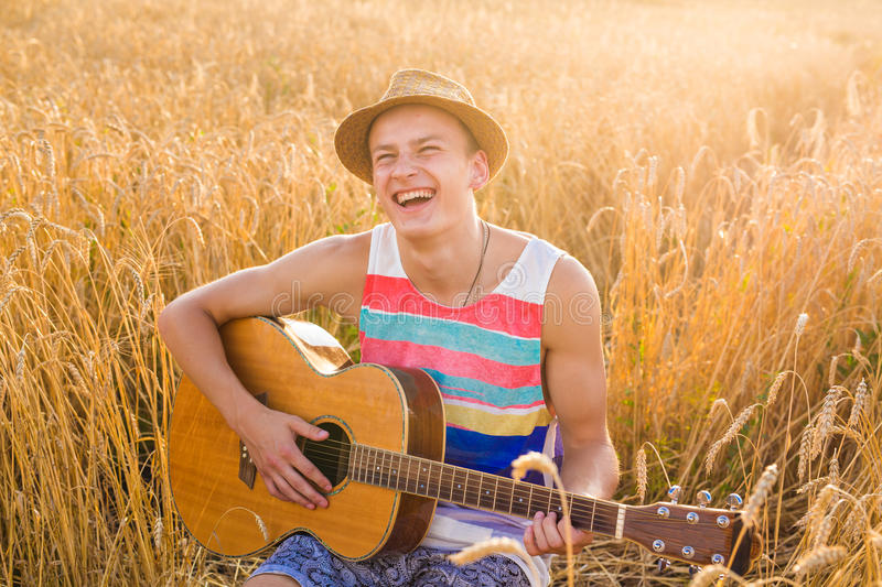 Happy handsome man is playing guitar in the field. Young man is playing guitar in the field stock photography