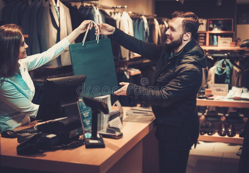 Happy handsome man taking shopping bag from saleswoman in a suit shop. stock images