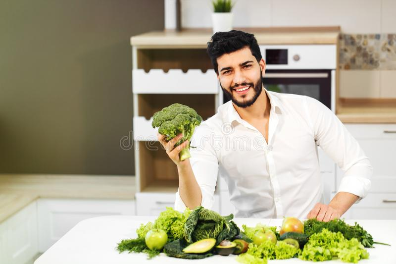 Man with Healthy Food. Happy handsome man in white shirt sitting at the table full of green healthy food royalty free stock photos
