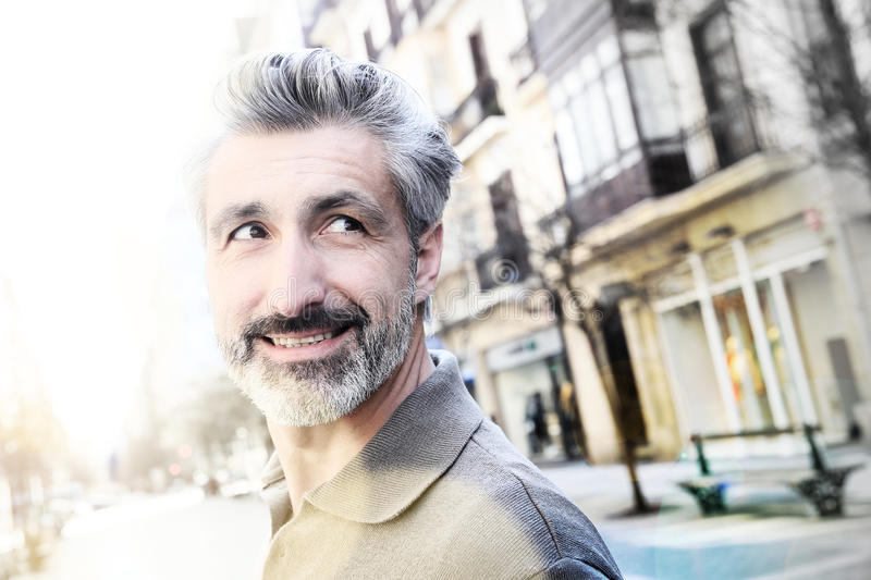 Happy handsome mature man walking in town stock images