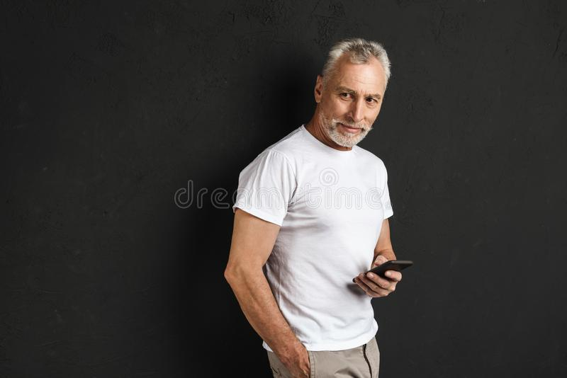 Happy handsome mature old man using mobile phone. royalty free stock photo