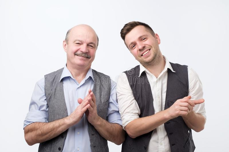 Happy handsome men applauding, clapping hands and looking away. royalty free stock images