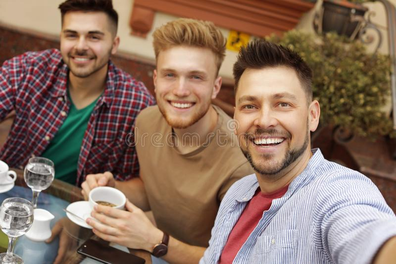 Happy handsome men taking selfie at cafe royalty free stock images