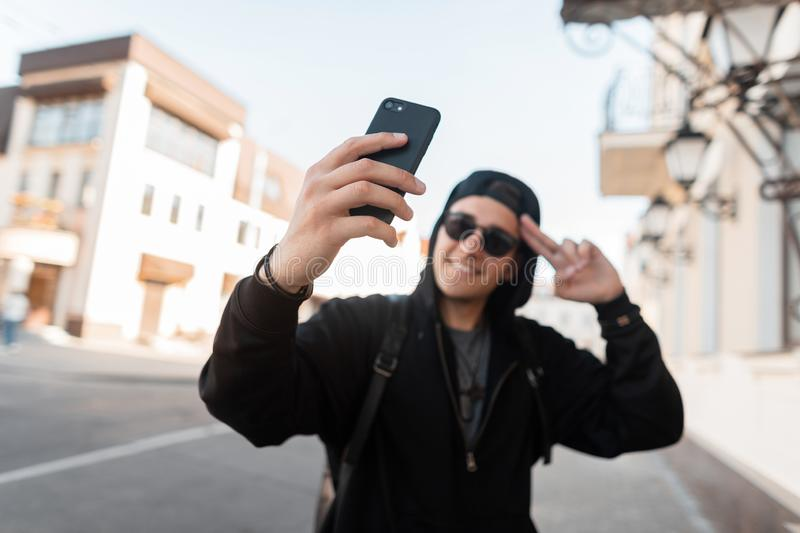 Happy handsome young hipster man in trendy hoodie hooded in stylish sunglasses in a cap with a cute smile makes the selfie royalty free stock images