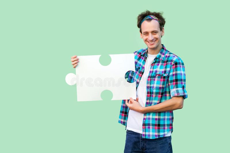 Happy handsome young adult man in checkered shirt standing and holding large piece of puzzle, looking at camera with toothy smile royalty free stock image