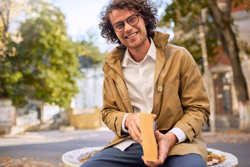 Happy handsome young man reading and posing with book outdoors. College male student carrying books in campus in autumn street. Smiling smart guy wears stock photo