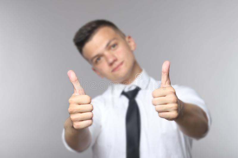 Happy handsome young man showing thumbs up stock images